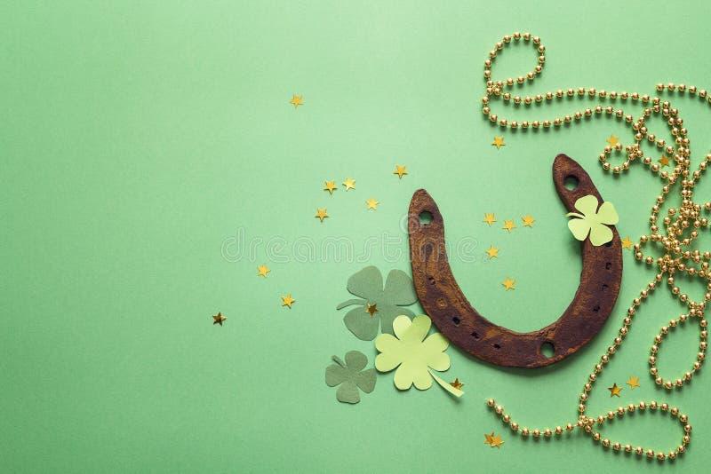 El fondo verde con el trébol oxidado de la herradura y del papel se va S imagenes de archivo