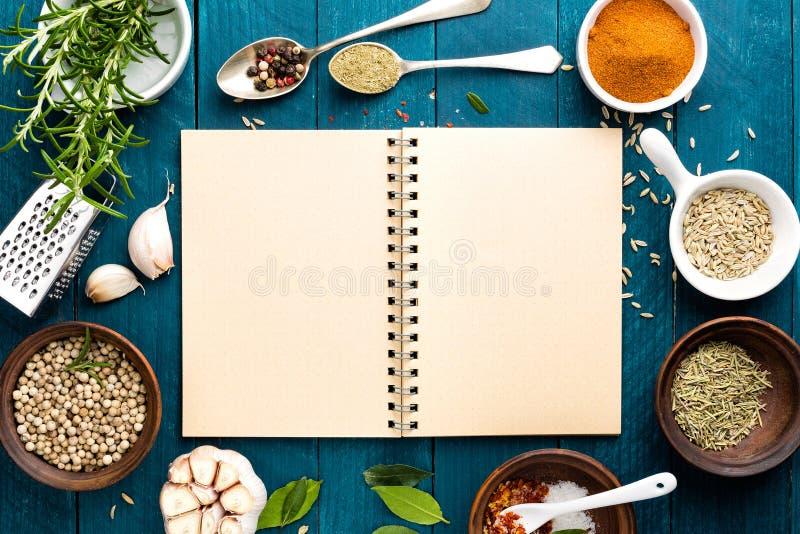 El fondo y la receta culinarios reservan con las especias en la tabla de madera fotografía de archivo libre de regalías