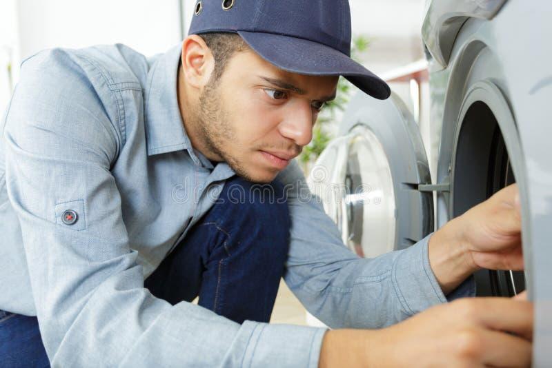 El fontanero del trabajador repara la lavadora en lavadero fotos de archivo libres de regalías