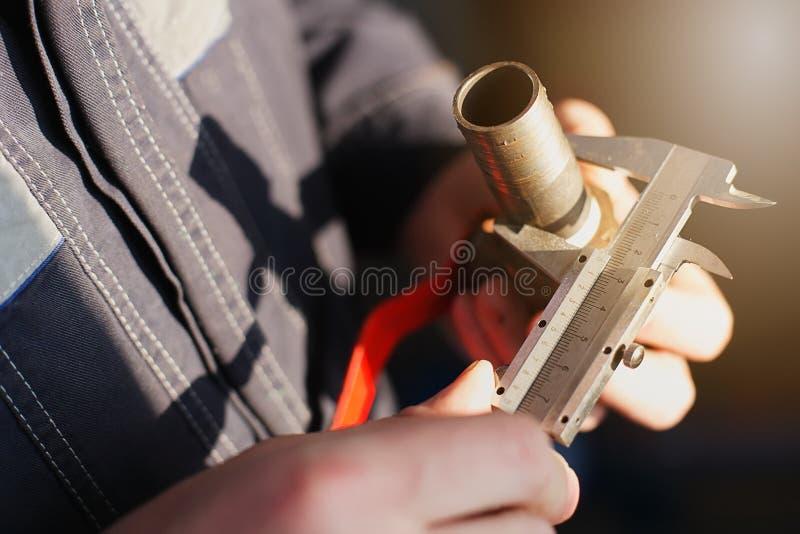 El fontanero mide el diámetro del tubo con un golpecito del calibrador para sondear imágenes de archivo libres de regalías