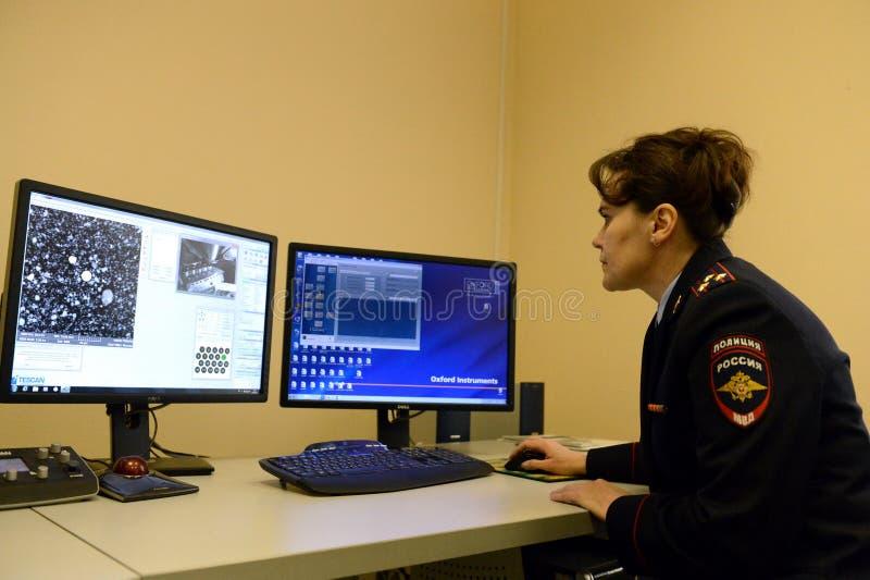 El forense criminal examina la composición elemental de la sustancia agarrada en la escena del crimen imagen de archivo