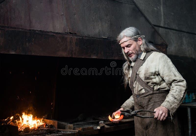 El forjador canoso forja el detalle en la herrería fotos de archivo
