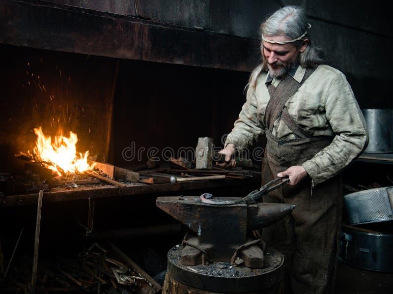 El forjador canoso forja el detalle en la herrería imagen de archivo