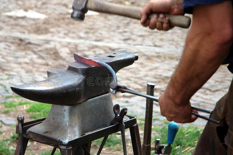 El forjador forja una herradura imagen de archivo