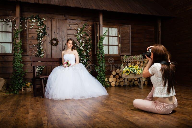 El fotógrafo atractivo joven está tomando a imágenes la novia en el estudio fotos de archivo