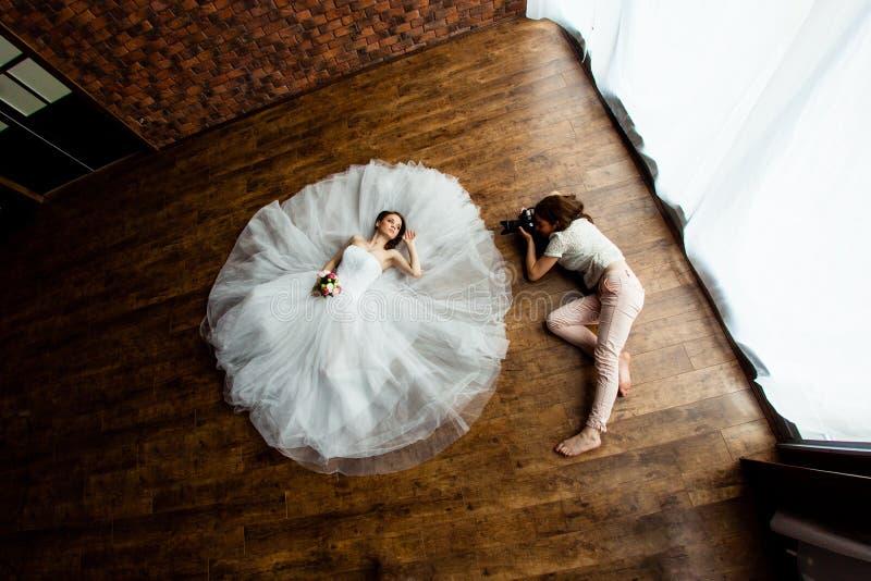 El fotógrafo atractivo joven está tomando a imágenes la novia en el estudio fotografía de archivo
