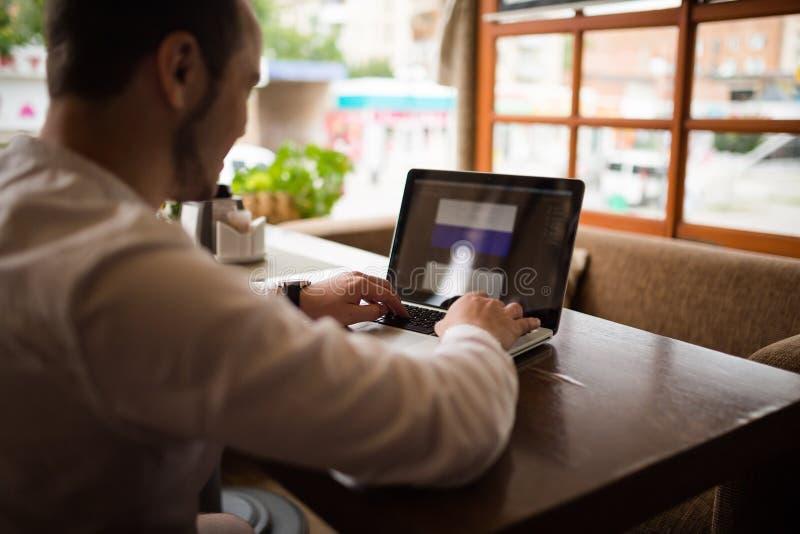 El fotógrafo con la cámara trabaja en su ordenador portátil fotos de archivo