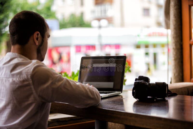El fotógrafo con la cámara trabaja en su ordenador portátil fotos de archivo libres de regalías