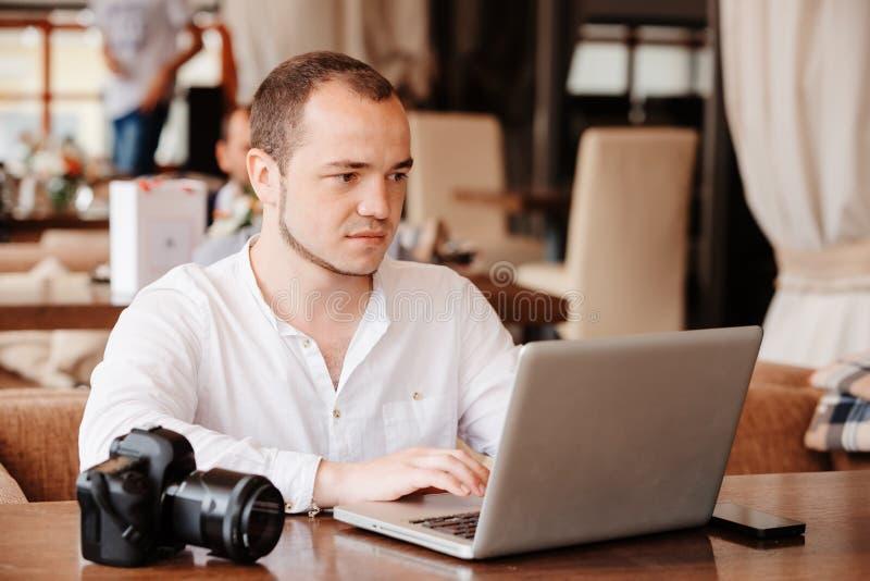 El fotógrafo con la cámara trabaja en su ordenador portátil imagenes de archivo