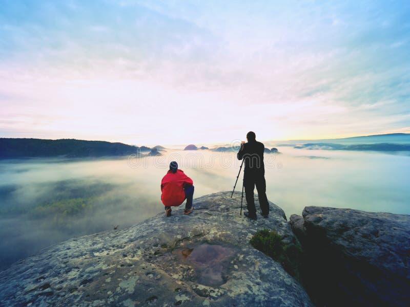 El fotógrafo con el ojo en el visor de la cámara en estancia del trípode en el acantilado y toma las fotos, amigos de la charla imagen de archivo