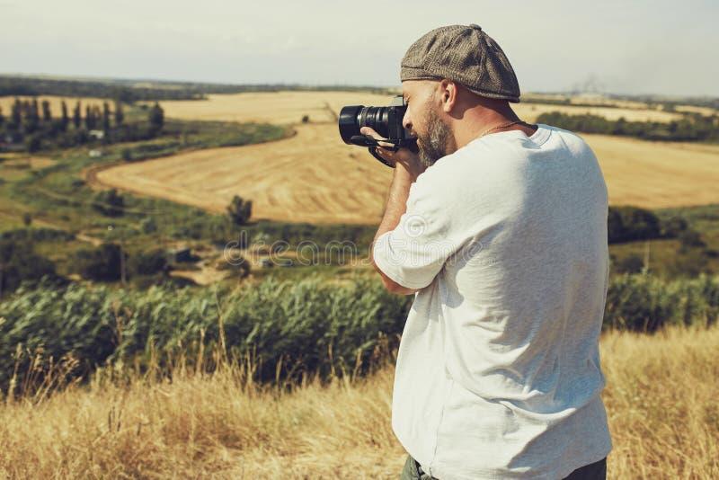 El fotógrafo con una cámara se coloca en el fondo de los campos de cereal pantalones cortos que llevan y una camiseta, un casquil fotos de archivo