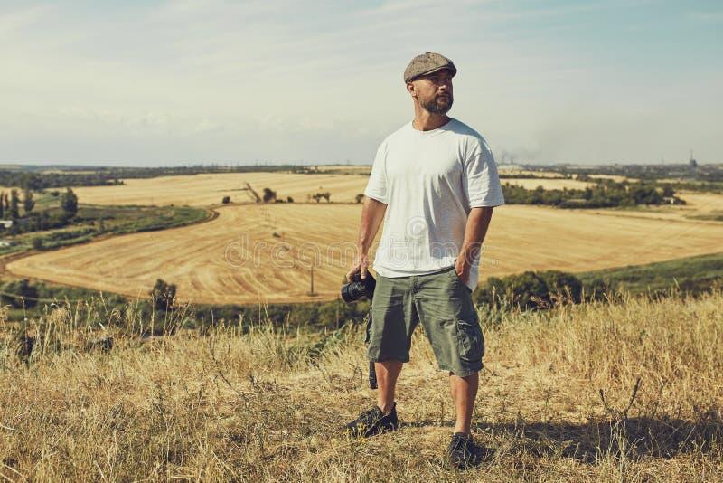 El fotógrafo con una cámara se coloca en el fondo de los campos de cereal pantalones cortos que llevan y una camiseta, un casquil imágenes de archivo libres de regalías