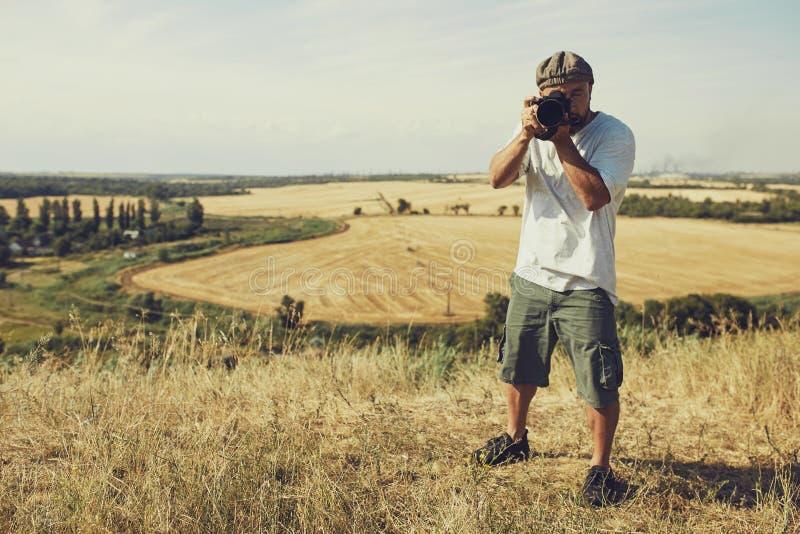 El fotógrafo con una cámara se coloca en el fondo de los campos de cereal pantalones cortos que llevan y una camiseta, un casquil imagen de archivo