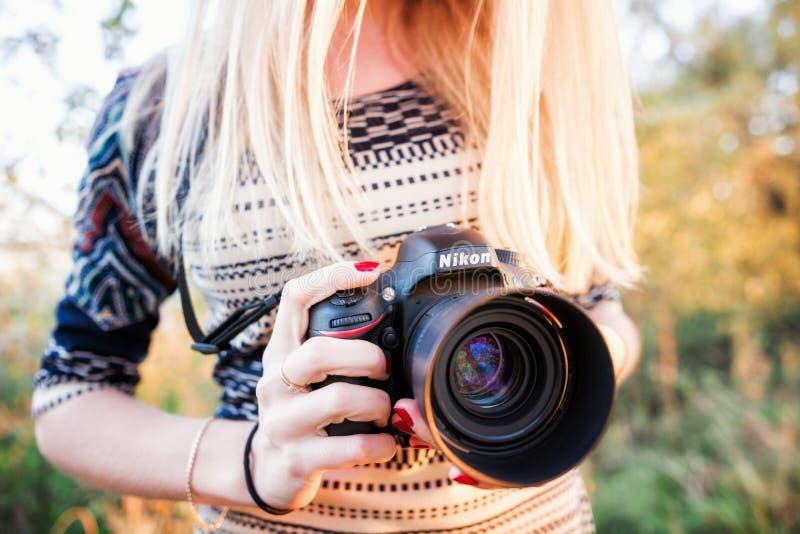 El fotógrafo de la muchacha sostiene la cámara y Nikkor 50m m f/1 de Nikon D610 lente 4G fotos de archivo
