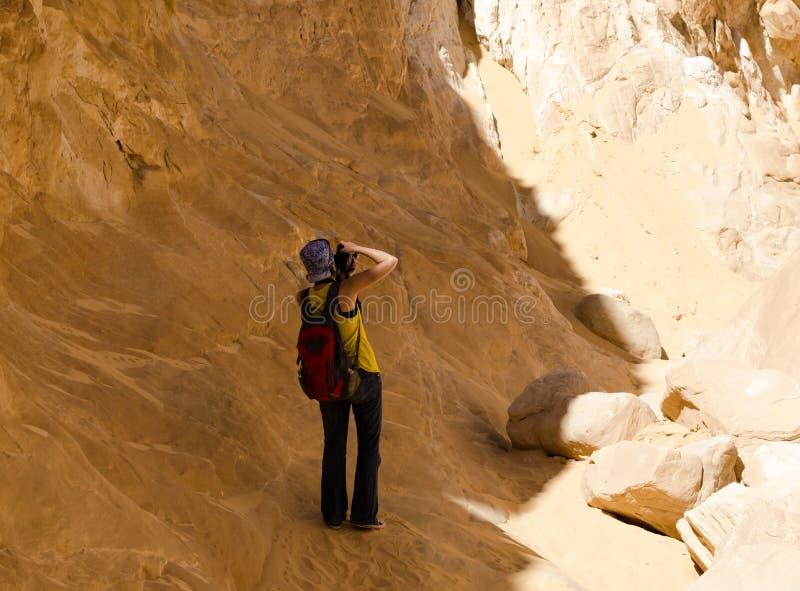El fotógrafo de la muchacha toma las imágenes de las montañas en el barranco en Egipto Dahab Sinaí del sur imagenes de archivo