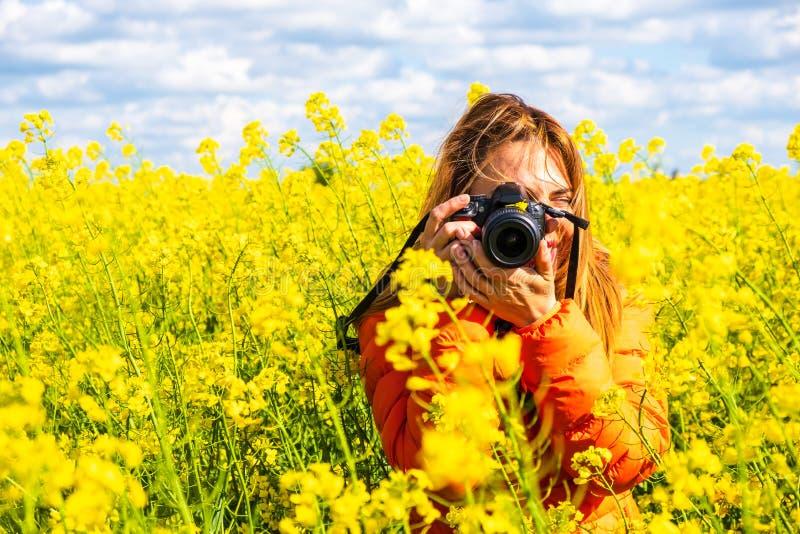 El fotógrafo de la mujer joven con un DSLR, llevando una chaqueta anaranjada, toma una imagen en un campo de la rabina, campo rur fotos de archivo libres de regalías