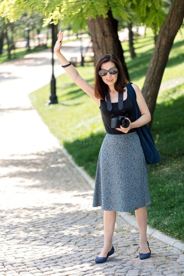 El fotógrafo de la mujer joven, turista sostiene una cámara y la agita imagen de archivo