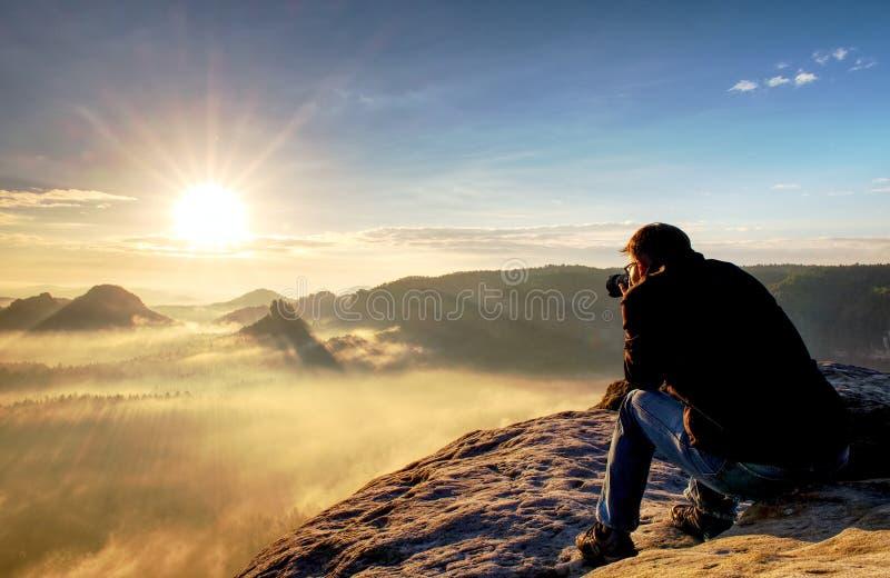 El fotógrafo de la naturaleza crea arte en punto de visión en montañas  fotos de archivo
