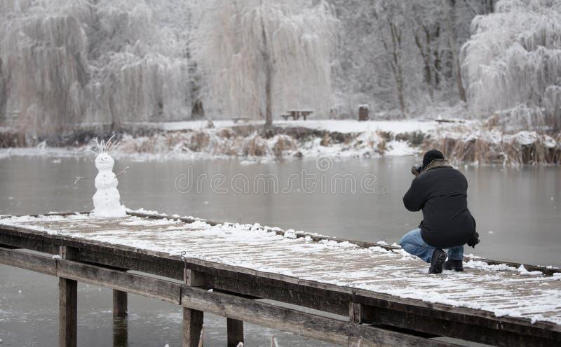 El fotógrafo de la naturaleza toma una foto de un muñeco de nieve imágenes de archivo libres de regalías