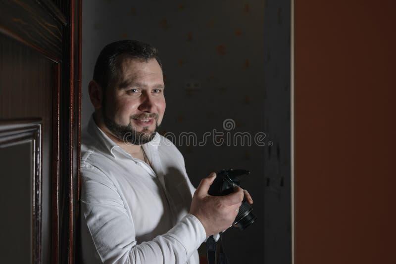 El fotógrafo de sexo masculino confiado joven en una camisa blanca está sosteniendo a foto de archivo