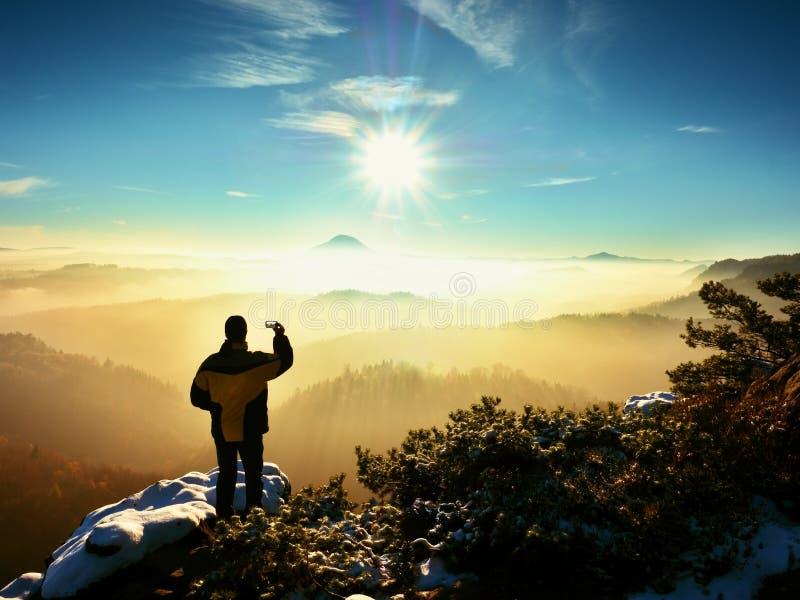 El fotógrafo del teléfono toma la imagen del paisaje montañoso del helada imagen de archivo
