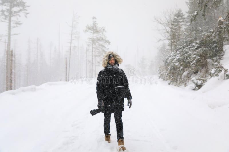 El fotógrafo en el camino del invierno en bosque foto de archivo libre de regalías