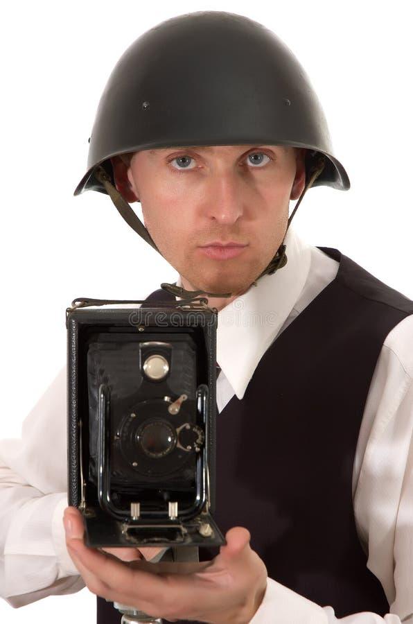 El fotógrafo en casco guarda para conseguir la cámara vieja foto de archivo