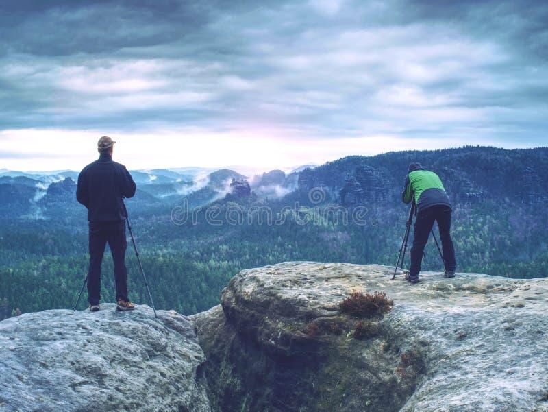 El fotógrafo está tomando una imagen del paisaje Dos hombres que caminan y que toman imágenes Campo, aventura, viaje y travelin foto de archivo