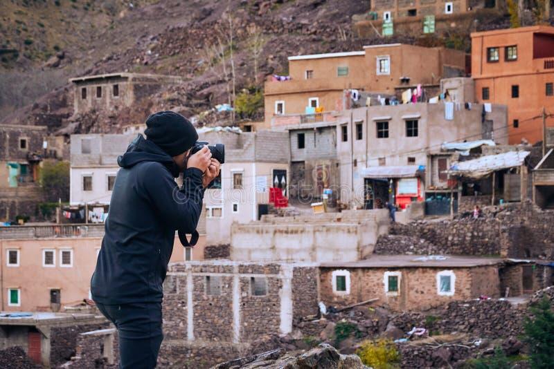El fotógrafo fotos de un paisaje que tiran de un pueblo rural marroquí imagen de archivo
