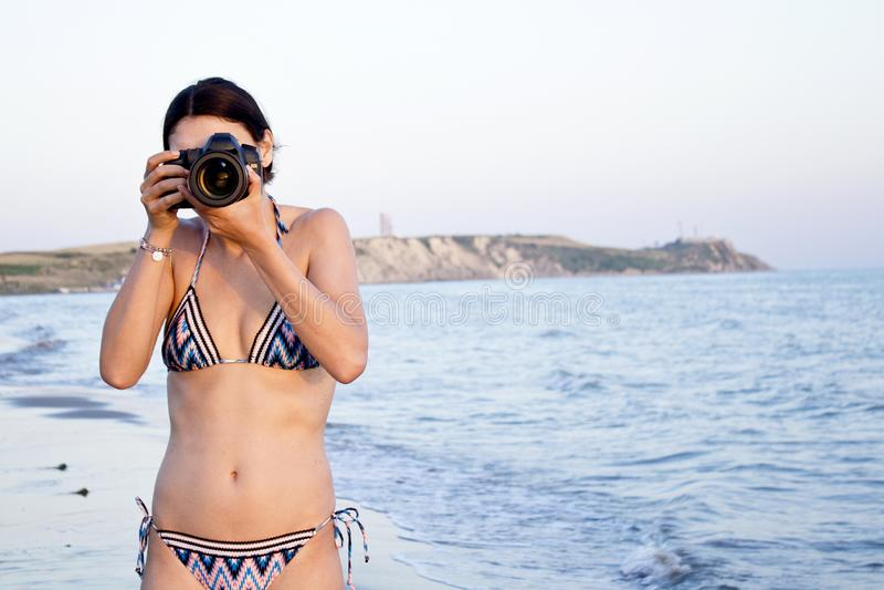 El fotógrafo hermoso de la mujer toma las fotos en bikini en la playa imagenes de archivo