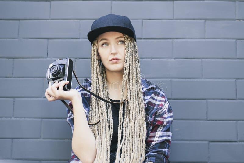 El fotógrafo hermoso joven de la mujer está sosteniendo la cámara foto de archivo
