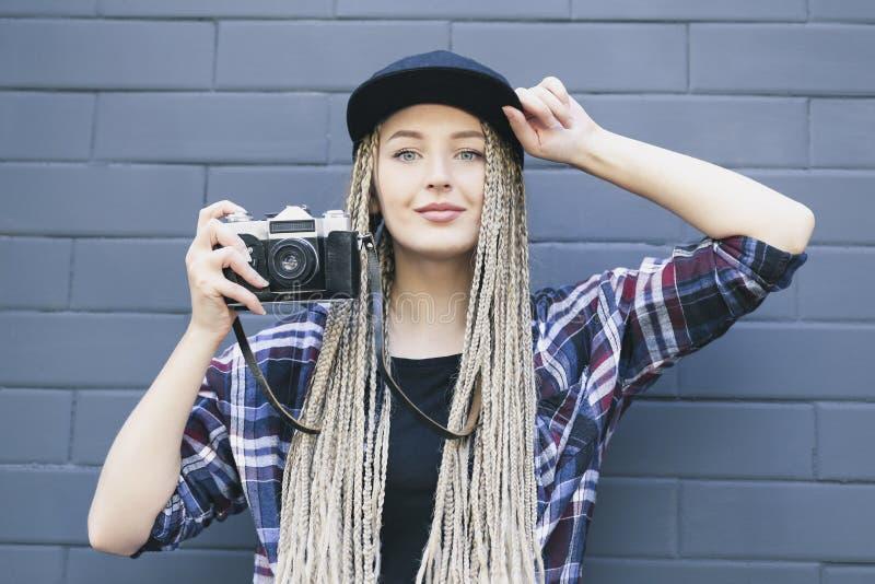 El fotógrafo hermoso joven de la mujer está sosteniendo la cámara fotos de archivo
