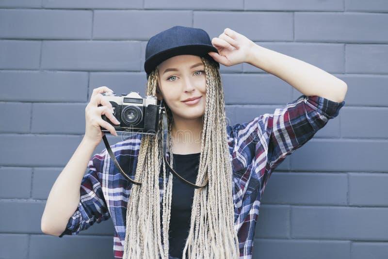 El fotógrafo hermoso joven de la mujer está sosteniendo la cámara imagen de archivo