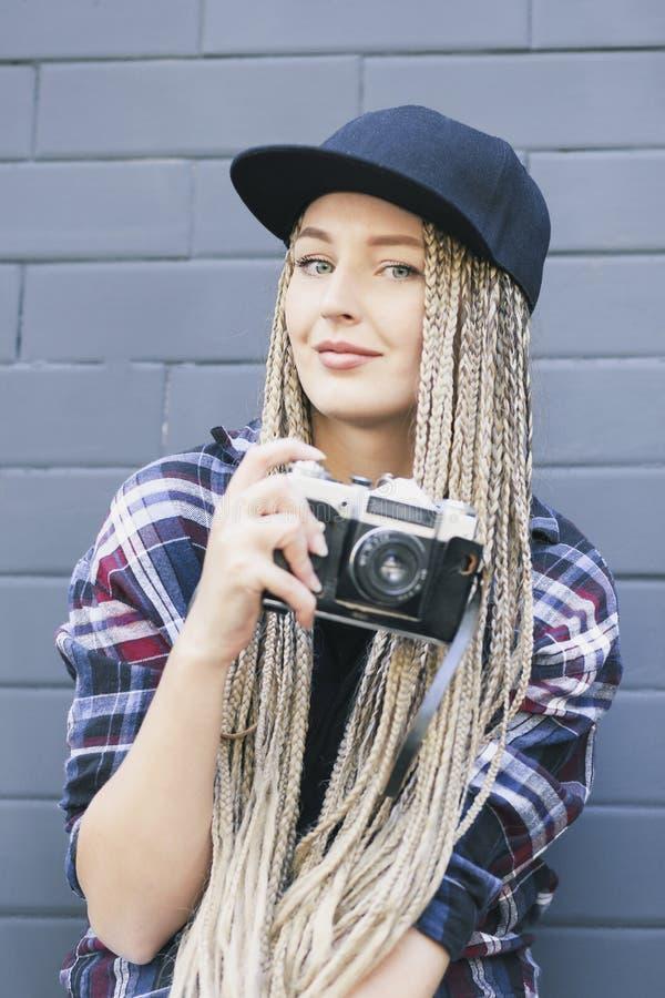 El fotógrafo hermoso joven de la mujer sostiene la cámara foto de archivo