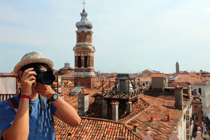 El fotógrafo joven con la cámara digital toma muchas imágenes en VE imágenes de archivo libres de regalías