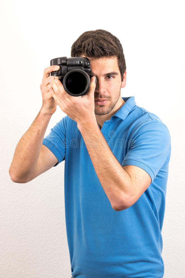 El fotógrafo joven mira a través de una cámara foto de archivo libre de regalías