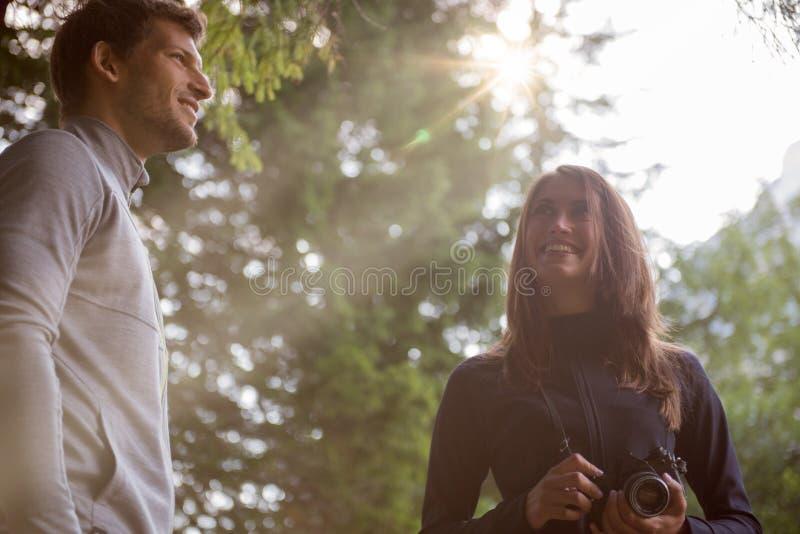 El fotógrafo sonriente del hombre y de la mujer en bosque del bosque con la llamarada del sol se enciende Grupo de aventura del v foto de archivo