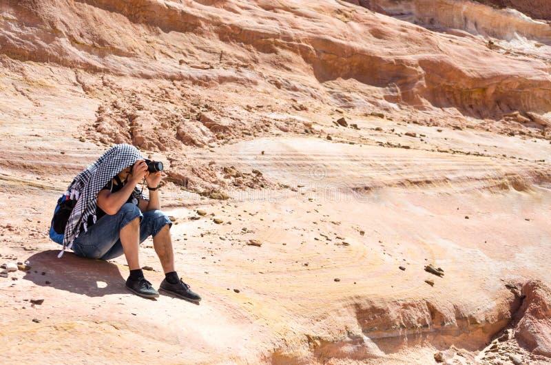 El fotógrafo toma las imágenes que se sientan en una roca en Egipto Dahab Sinaí del sur fotografía de archivo libre de regalías