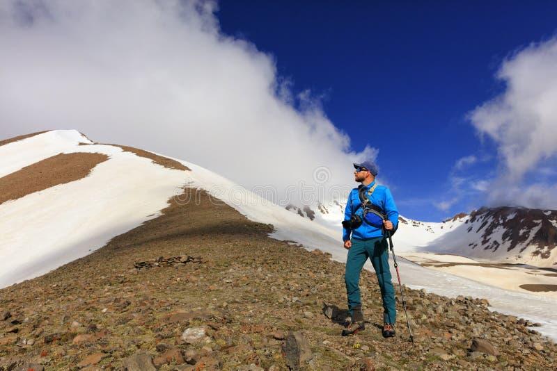 El fotógrafo turístico examina el top de una montaña nevada y se prepara para subir fotos de archivo libres de regalías