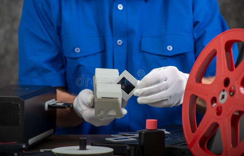 El fot?grafo de la mano convierte la diapositiva de pel?cula a digital para ahorrar fotos de archivo