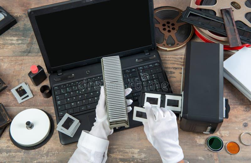 El fot?grafo de la mano convierte la diapositiva de pel?cula a digital para ahorrar fotografía de archivo libre de regalías