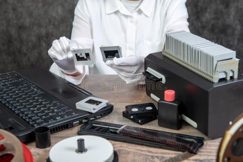 El fot?grafo de la mano convierte la diapositiva de pel?cula a digital para ahorrar fotos de archivo libres de regalías