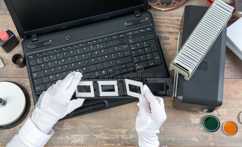El fot?grafo de la mano convierte la diapositiva de pel?cula a digital para ahorrar imágenes de archivo libres de regalías