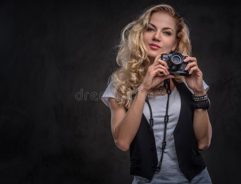 El fot?grafo rubio rizado sensual de la muchacha vestido en una camiseta y un chaleco blancos lleva muchos accesorios y imagen de archivo libre de regalías