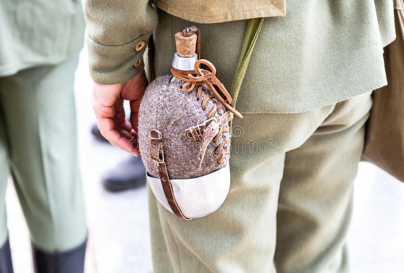 El frasco militar del vintage cuelga en una correa de un soldado fotografía de archivo libre de regalías