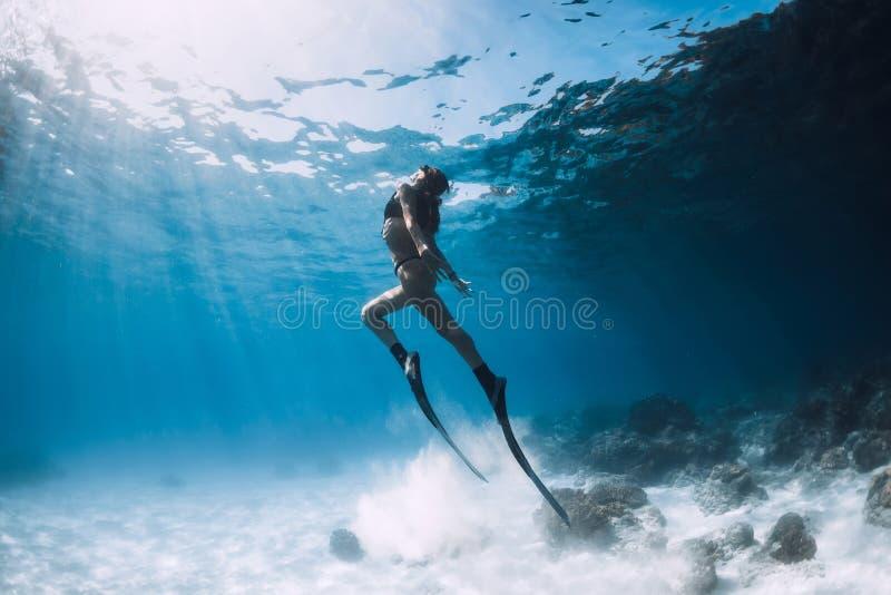 El freediver de la mujer se desliza sobre el mar arenoso con las aletas foto de archivo libre de regalías