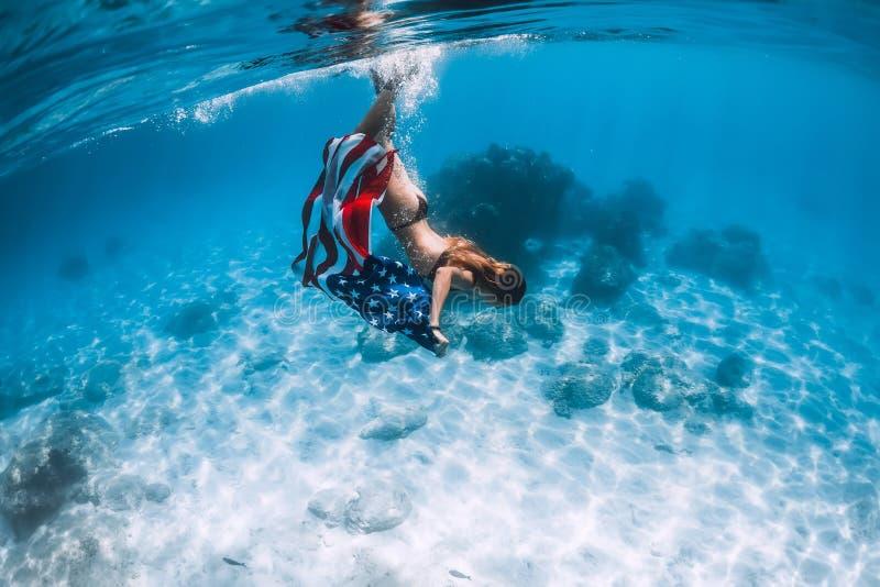 El freediver de la mujer se desliza sobre parte inferior de mar arenosa con la bandera de Estados Unidos imagen de archivo