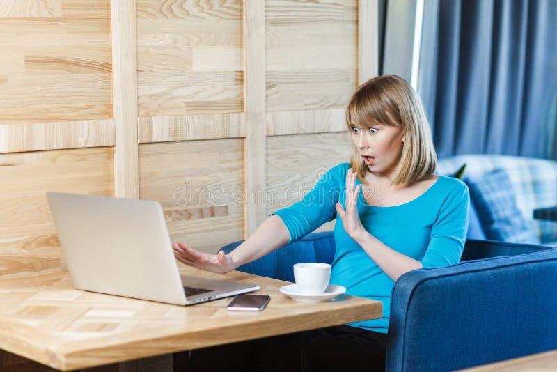 El freelancer asustado emocional de la chica joven en blusa azul se está sentando en café y el griterío a la causa del laptope in fotos de archivo libres de regalías