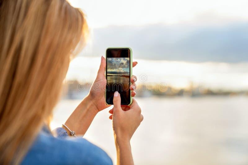El freelancer de la muchacha en la puesta del sol habla en el teléfono y trabaja imágenes de archivo libres de regalías