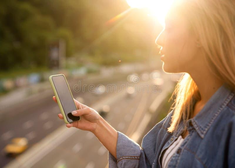 El freelancer de la muchacha en la puesta del sol habla en el teléfono y trabaja fotos de archivo